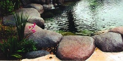 Synthetic rocks surround a backyard pond and add to the overall aesthetic