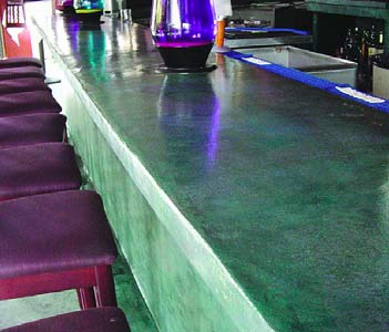 A vibrant green concrete countertop in a high-end bar establishment.