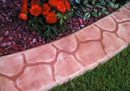 Decorative concrete curbing is used as edging along flower beds.