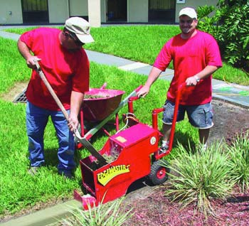 Two concrete contractors standing with their easy to use concrete curbing machine.