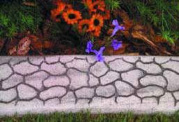 Concrete curbing with texture of individually placed stone and colored grout.