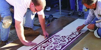Laying down ornate stencils on a concrete surface