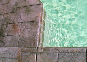 Pool deck with stamped concrete and colored with brown stains.