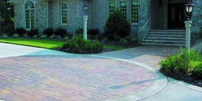 Large stamped concrete patio in front of a mammoth house