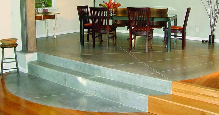 GLC3 Concrete finished concrete in a dining room made a circle of light gray concrete cut to mimic tile as it flows down the stairs.