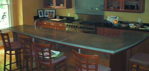 L shaped concrete countertop island in a kitchen where metakaolin was used to harden the concrete.