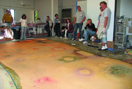 Spray water-based dyes on the whole floor.The objects act as resists for the dyes.