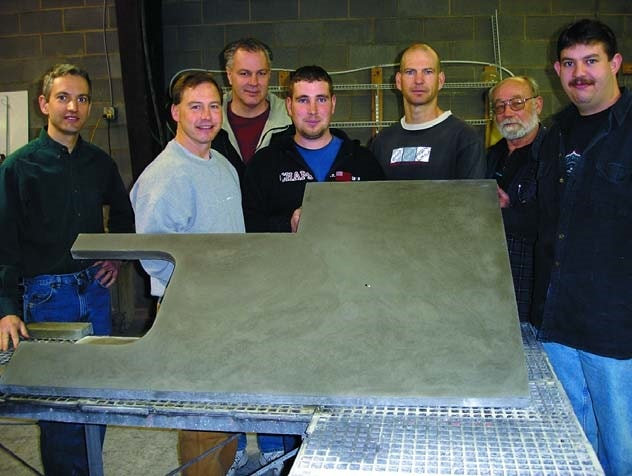 Jeffrey Girard with students holding up a precast concrete countertop at Concrete Countertop Institute.