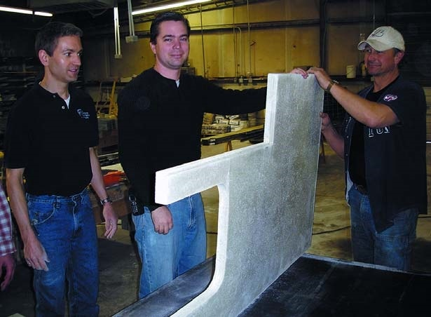 Jeffrey Girard with students standing a precast concrete countertop to inspect the under side at Concrete Countertop Institute.