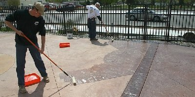Two men using a concrete sealer to finish off a beautiful outdoor decorative concrete patio.