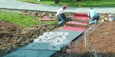 KML Finishers prepare steps for using concrete release agent and then stamping a concrete sidewalk.