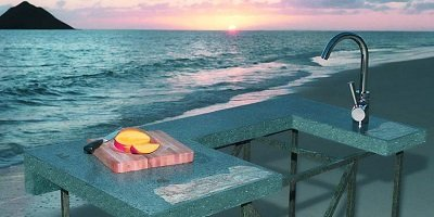 Camp style concrete countertop on a Hawaiian beach with a sunset in the background over the ocean.