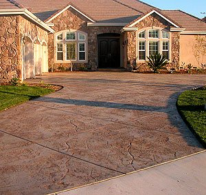 stamped curved driveway - An example of how driveway curves match a residence's arches. Notice how naturally the driveway blends with the landscape and culture stone.