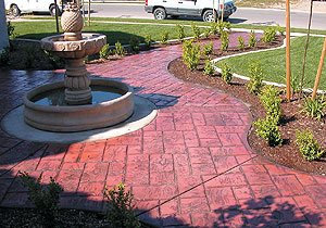 curved stamped walkway - Planter beds are used to protect sealer from lawn sprinklers.