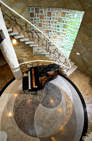 Spectacular Bomanite project surrounding a grand piano near a winding stair case.