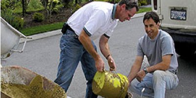 Two men with yellow bucket mixing concrete using a product from Lafarge.