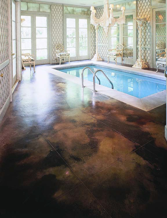 Inviting indoor swimming pool with a concrete deck colored in a rich chocolate brown Kemiko Concrete Product stain.