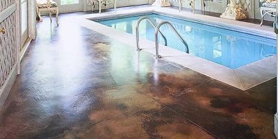 Elegant indoor swimming pool deck in a rich brown Kemiko concrete stain color invites.