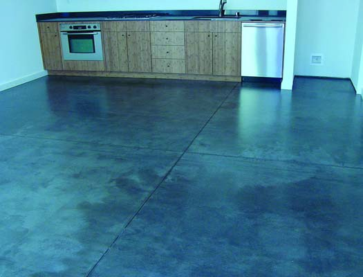 Concrete floor in new apartment building was too damaged for regular concrete stains so the contractor used a polyurea floor coating to mask the damage and stains.