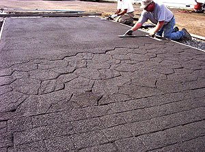 Pervious Concrete being stamped. Pores in pervious concrete can become filled with silt and other particulate matter. This can affect appearance, particularly if the fill is deeper in some portions of the slab than in others.