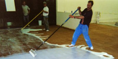 Retro man applying sealer to acid stained concrete, leaning way back.