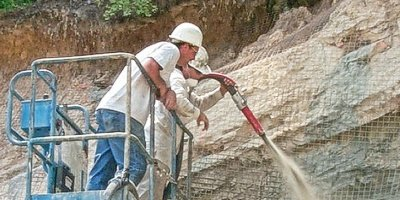 Concrete contractor spraying shotcrete on a hillside from a lift.