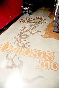 Floor Seasons used a stencil to get the Ozmosis Inc logo on the concrete floor.