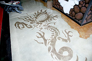 A stencil was used to create this dragon in a deeper acid stained color next to the light concrete floor.