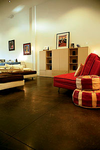 Deep colored concrete floor in a serene living room with a red sitting chair.