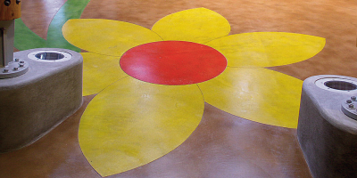 Bright yellow flower with a red center on a concrete surface using concrete stains.