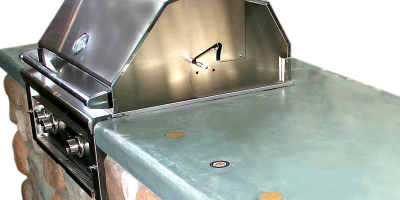 River rock base on outdoor bbq with a concrete countertop