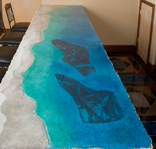 Top view of a concrete counter featuring a ocean theme from deep ocean blue to the sandy beach with shells