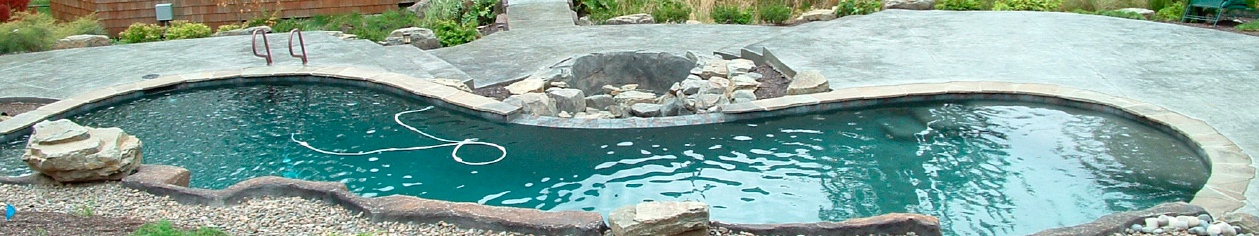 long pool surrounded by concrete rocks and a concrete deck that is stamped and textured.