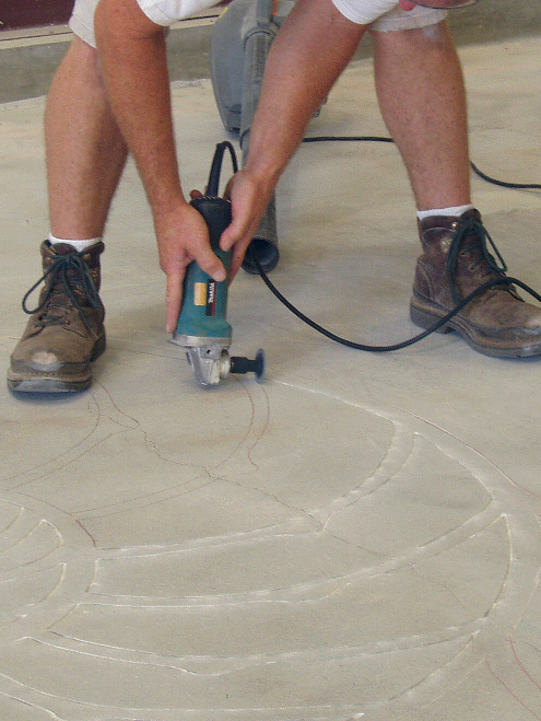 Bob Harris using a grinder to engrave a concrete floor with a 2 inch blade.