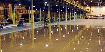 A large warehouse with men working on the polishing of the floor instead of covering the concrete with another flooring option.