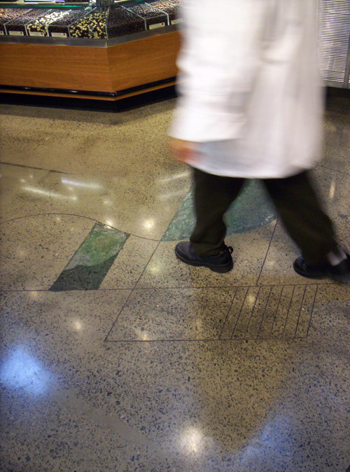 Butcher in a white coat walking across a polished and dyed concrete floor.