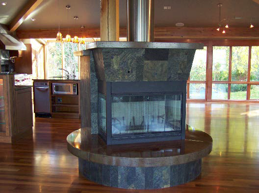 Concrete surrounds this wood burning fireplace.