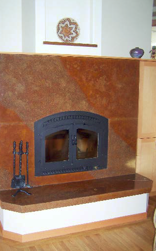 Concrete fireplace and hearth in orange and browns.