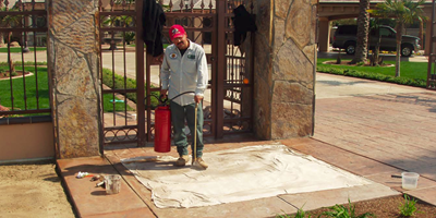 a concrete contractor sprays a driveway with concrete stain using a sprayer