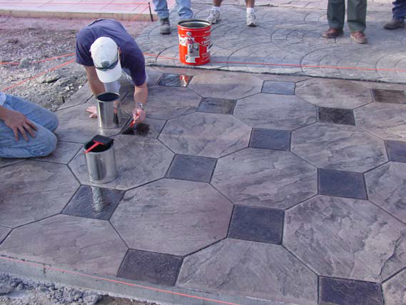 Using acid stain to vary the color of each stone on a stamped concrete slab.