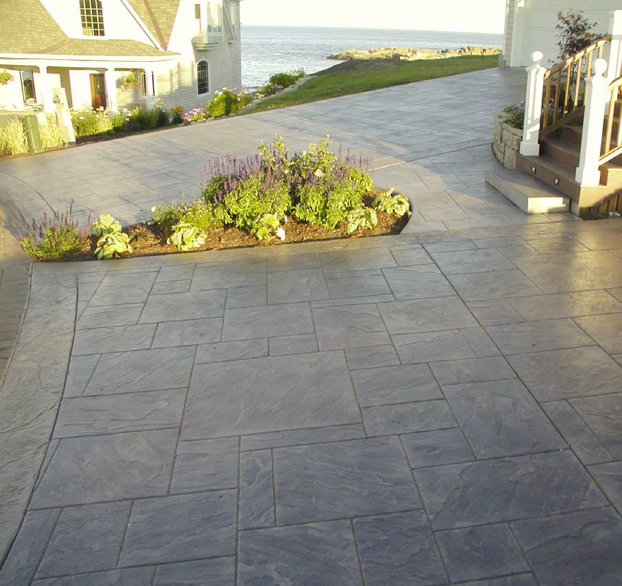 Large driveway with stamped concrete and a planter included to bring a punch of nature.