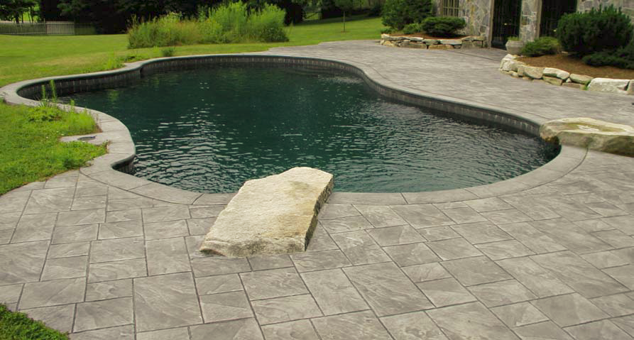 Concrete pool deck surrounds this pool in a natural setting.