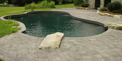 The decorative concrete surrounding this pool/pond has been stamped..