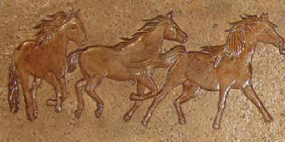 Horses stamped into concrete and stained a reddish brown color.