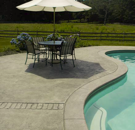 Concrete pool deck with a patio furniture set.