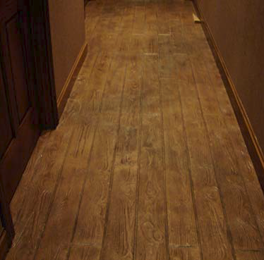 With the range of products available today, artisans in the decorative and faux markets have almost unlimited design capabilities. Here a faux wood plank look down the hallway accomplished stain.