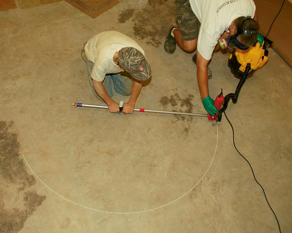 Two people are cutting concrete following the pattern made with the quick draw design and layout too.