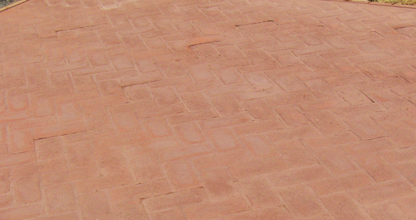 Brick-like stamped concrete has been colored with dust-on color hardener.