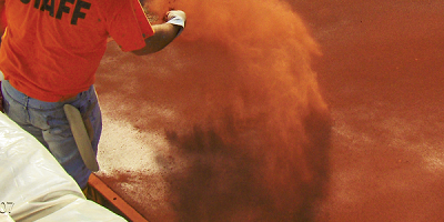 Tossing red color hardener onto a slab of concrete.