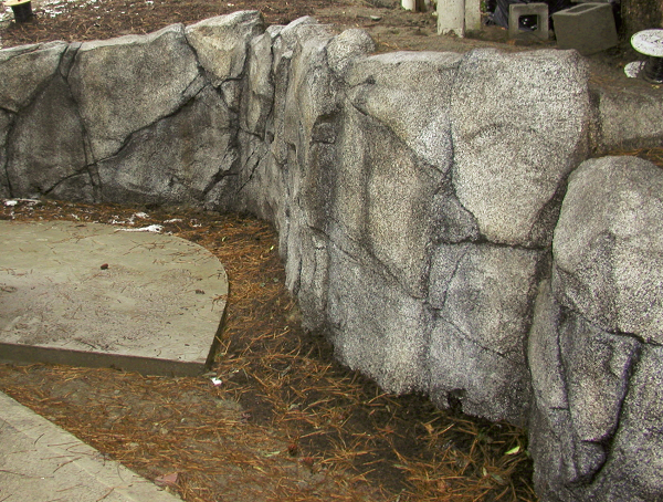 Large boulder like retaining wall that is created out of concrete.
